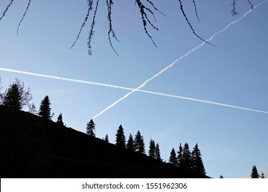 a cross from vapor trails on the sky with tree silhouettes on foreground