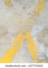 Cross yellow lines on the concrete floor. grunge signs of the markings, background texture