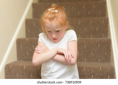 Cross young girl sitting on the naughty step with her arms folded and a angry look on her face showing lots of emotion.