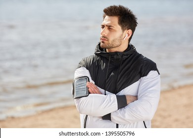 Cross-armed athlete in windbreaker listening to music in airpods while having break after training on the beach
