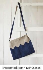 Crossbody bag hangs on a white wooden ladder. Linen bag. Knitted blue decor. Light background
