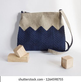 Crossbody bag is made of linen and decorated with knitted blue decor. Light background
