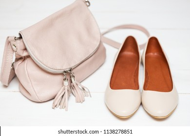 cross-body handbag and shoes on a white background