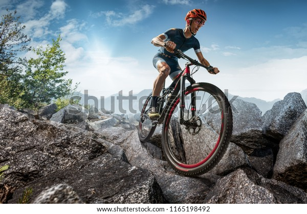 Cross-Country biker on stone trail. Male cyclist rides the rock