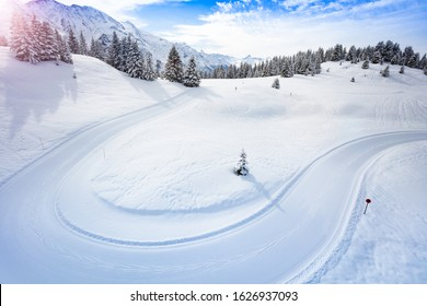 Cross-country ski piste path in the mountains on good weather winter day.