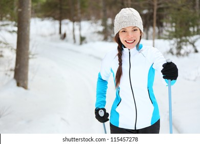 Cross-country skiing woman doing classic nordic cross country skiing in trail tracks in snow covered forest in Quebec, Canada