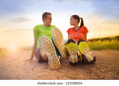 Cross-country trail running couple stretching and exercising at sunset
