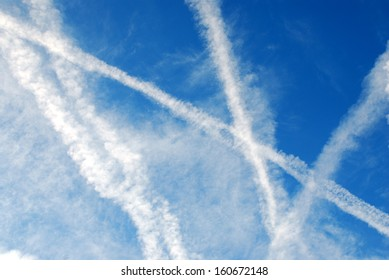 Crossed airplane condensation trails, slightly dispelling, on blue sky