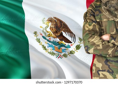 Crossed arms Mexican soldier with national waving flag on background - Mexico Military theme.