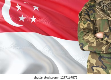 Crossed arms Singaporean soldier with national waving flag on background - Singapore Military theme.