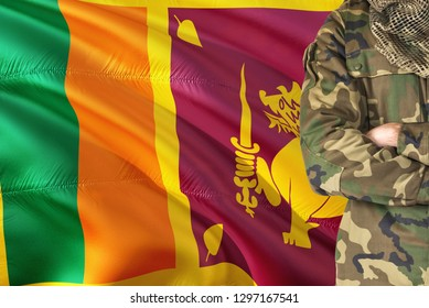 Crossed arms Sri Lankan soldier with national waving flag on background - Sri Lanka Military theme.