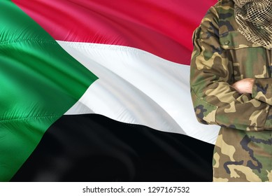 Crossed arms Sudanese soldier with national waving flag on background - Sudan Military theme.