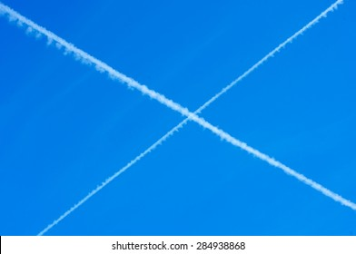 Crossed chem trails of planes in blue sky