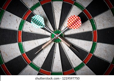 Crossed Darts On Dart Board. darts lie on dartboard
