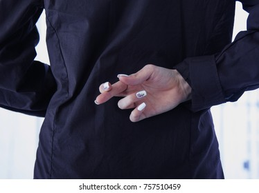 Crossed fingers as a symbol of deceit and double standards at work in business (Body language, gestures, psychology, emotion)