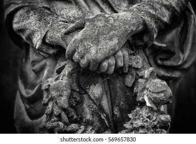 Crossed hands of an angel statue holding a wreath in black and white