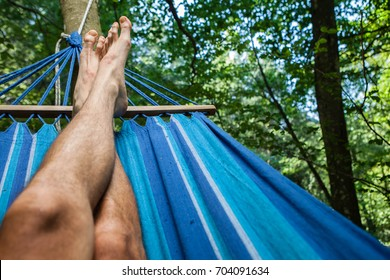 Crossed legs of a man lying on a hammock in the woods. Illuminated from above. Barefoot.