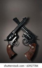 Crossed Revolver Guns on Dark Background