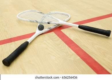 crossed squash rackets and ball on the wooden floor. Racquetball equipment on the court near red line. Photo with selective focus