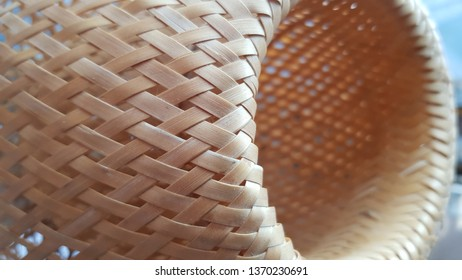 Crossed straw woven texture. Wicker lampshade closeup. Natural straw lattice texture. Round shaped geometry background. Light beige grid lamp. Geometric shapes and lines abstract backdrop. 3D shapes