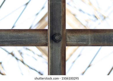 Crossed two metal beams fastened in the center by a bolt and nut. Bottom view with blurry background.