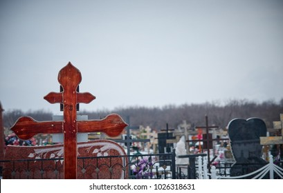 crosses in the cemetery, the monuments of the dead, cemetery in winter, wreaths, artificial flowers