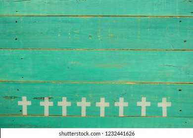 Crosses hanging on blank antique rustic mint green wooden background;  religious holiday and spiritual background with painted wood copy space