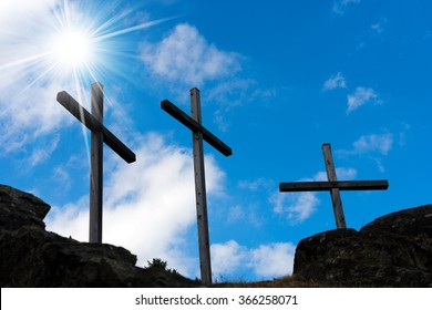 Crosses Silhouette against Blue Sky / Silhouette of three crosses against a blue sky with clouds and sun rays. Carisolo Trentino Italy