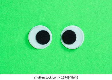 Cross-eyed googly eyes on neon green background, mad funny toys eyes close-up.