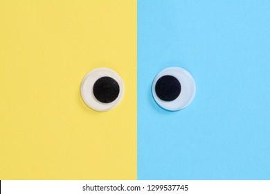Cross-eyed googly eyes on yellow-blue background, mad funny toys eyes close-up.