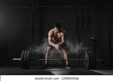 Crossfit athlete clapping hands and preparing for weight lifting at the gym. Barbell magnesia protection dust cloud. Handsome man doing functional training. Practicing powerlifting. Workout exercises.