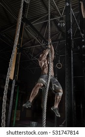 crossfit athlete climbing the rope in gym