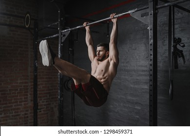 Crossfit athlete doing abs exercises on horizontal bar. Practicing calisthenics at gym.