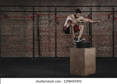 Crossfit athlete doing box jump exercise at the gym. Man practicing functional training. Copy space
