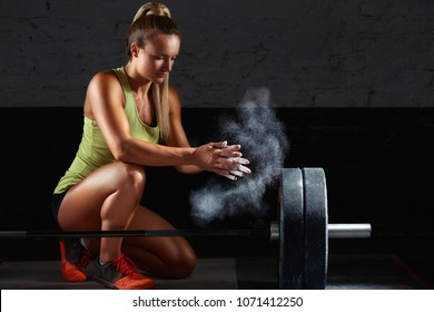 Crossfit female weightlifter preparing for her workout chalking her hands magnesia chalk preparation fitness athletics activity leisure lifestyle power confidence motivation concept