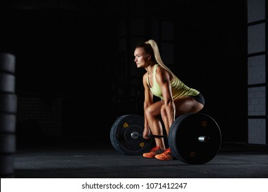 Crossfit and fitness. Horizontal shot of beautiful young fitness woman exercising with heavy dumbbell in dark gym studio. Deadlift bodybuilding fitness WOD workout power strength energy pumping