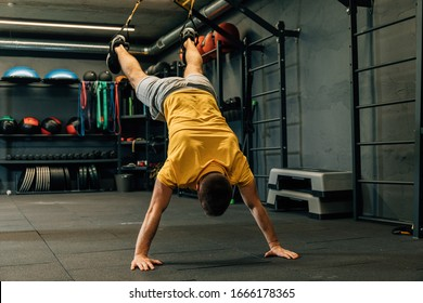 Crossfit fitness trx push ups man workout at gym. Strength and concentration. Young handsome man in sportswear exercising at gym.