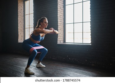 Crossfit healthy concept. Woman wearing sport clothing using resistance band - Shutterstock ID 1788745574
