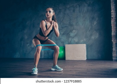 Crossfit healthy lifestyle concept. Nice chaming adorable beautiful sporty muscular fitness model lady wearing sports panties and top with blue elastic band on legs muscles doing sit-ups