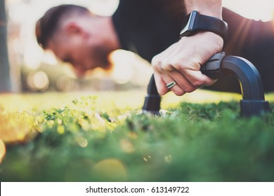 Crossfit lifestyle concept.Closeup view of male hand while doing pushups in the park on the sunny morning.Training outdoors.Fit shirtless male fitness healthy model in exercise outdoors.Blurred