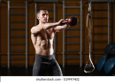 Crossfit training. Fitness man doing a weight training by lifting kettlebell. Young athlete doing kettlebell swings. Bodybuilder lifting kettlebell. Crossfit instructor at the gym. Crossfit in the gym