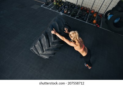 Crossfit woman exercising at gym. Muscular female flipping huge tire