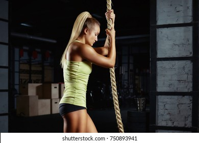 Crossfit woman preparing for rope climbing exercise at the local gym muscles power strength focus concentration preparation competitive beauty fitness active living. Crossfit-lifestyle, battle rope