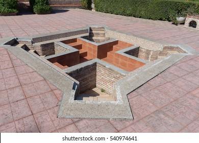 Cross-formed pool in St. Ephrem the Syrian monastery courtyard. Kondariotissa, Pieria, Greece.