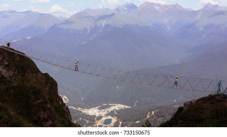 The crossing of the abyss in the mountains .People go on rope bridge across the chasm.