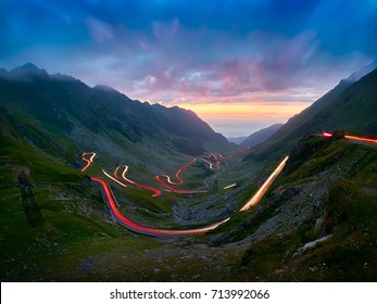 Crossing Carpathian mountains in Romania, Transfagarasan is one of the most spectacular mountain roads in the world - cloudy day at dusk with car lights trails on road