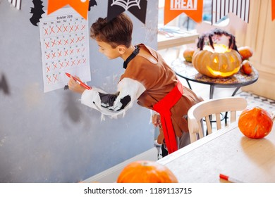 Crossing day. Dark-haired boy wearing skeleton Halloween costume crossing the last day of October on his wall calendar