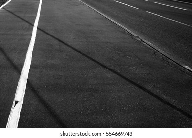 Crossing lines of a bicycle path marking, an automobile road markup, a curb and shadows of pillars. Russia, Moscow, May 2015.