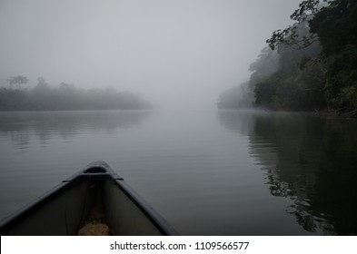 Crossing the Moa river by canoe to Tiwai Island Wildlife Sanctuary during foggy early morning, Sierra Leone, Africa