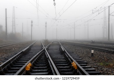 Crossing railways disappearing in the mist in autumn morning